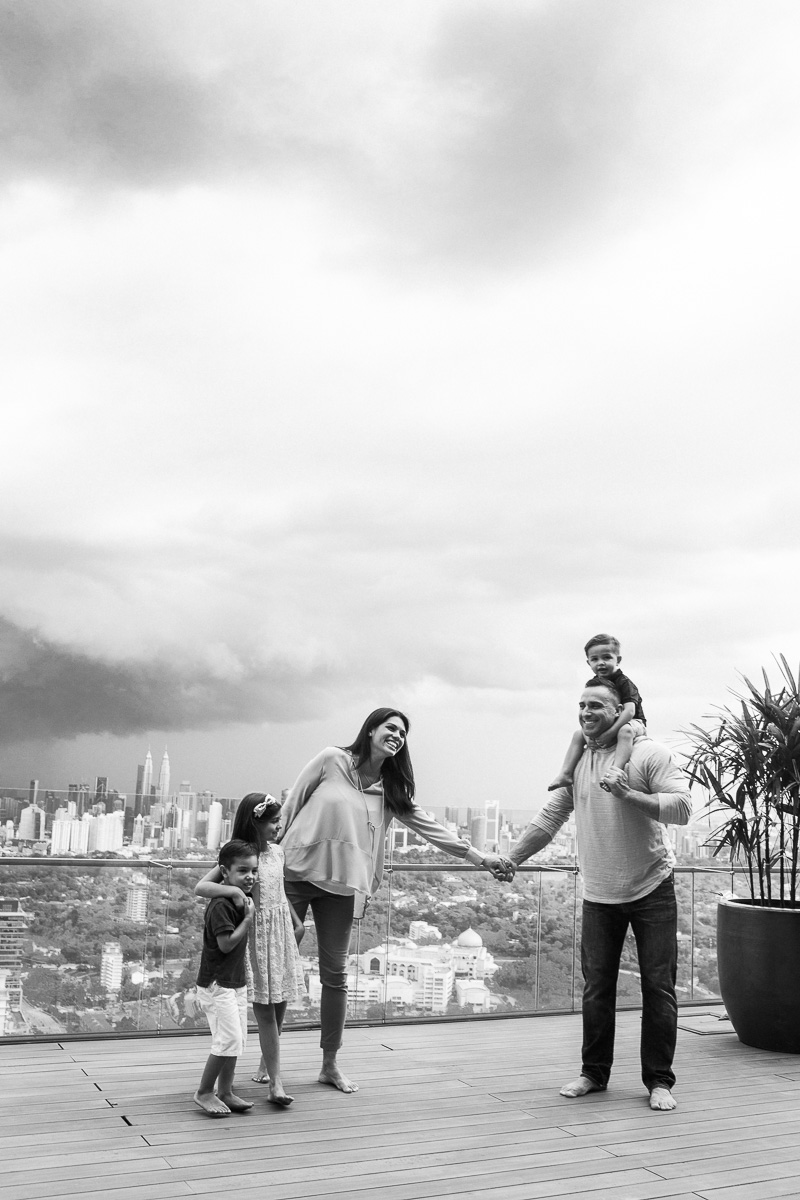 a family holds hands while the stunning kuala lumpur skyline is fatured from behind.