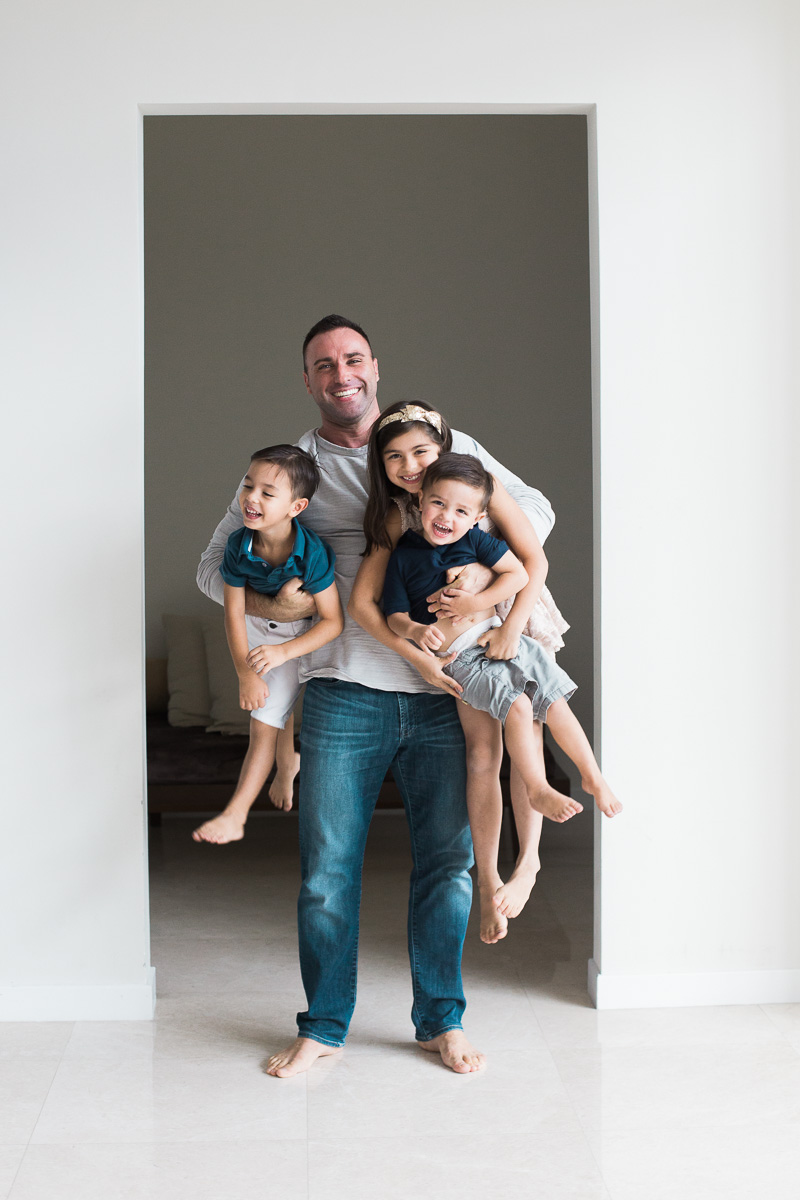 A dad holds three children at once. A family photography session in Kuala Lumpur.