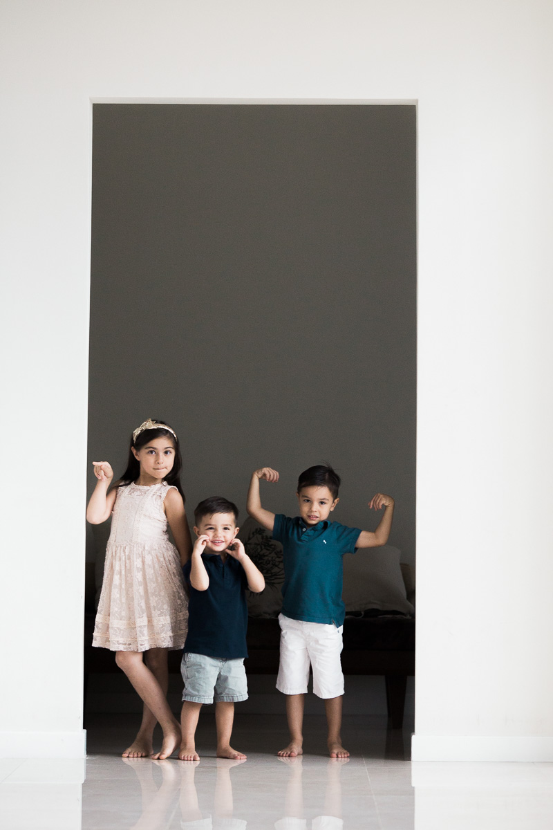 Three children pose with their muscles by Kuala Lumpur Photographer erica knecht