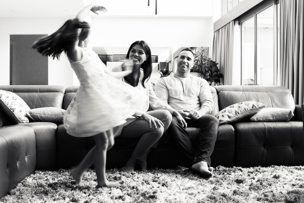 A little girl dances while her loving parents look on as captured by top asia family photographer erica kecht