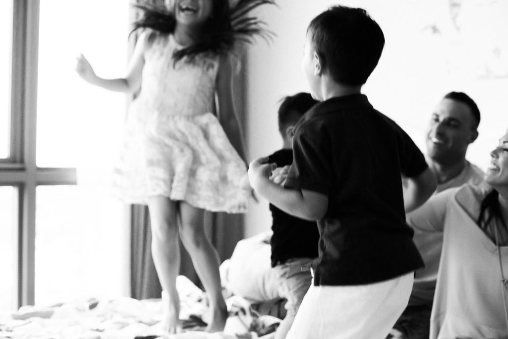 A happy little girl in a beautiful dress jumps on the bed in Kuala Lumpur by family photographer erica knecht