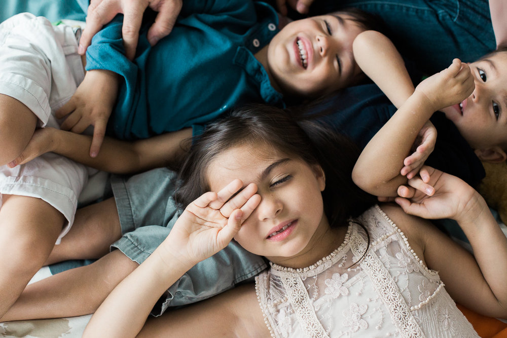 three kids cuddle together in a powerful image created by asia's top family photograher erica knecht.