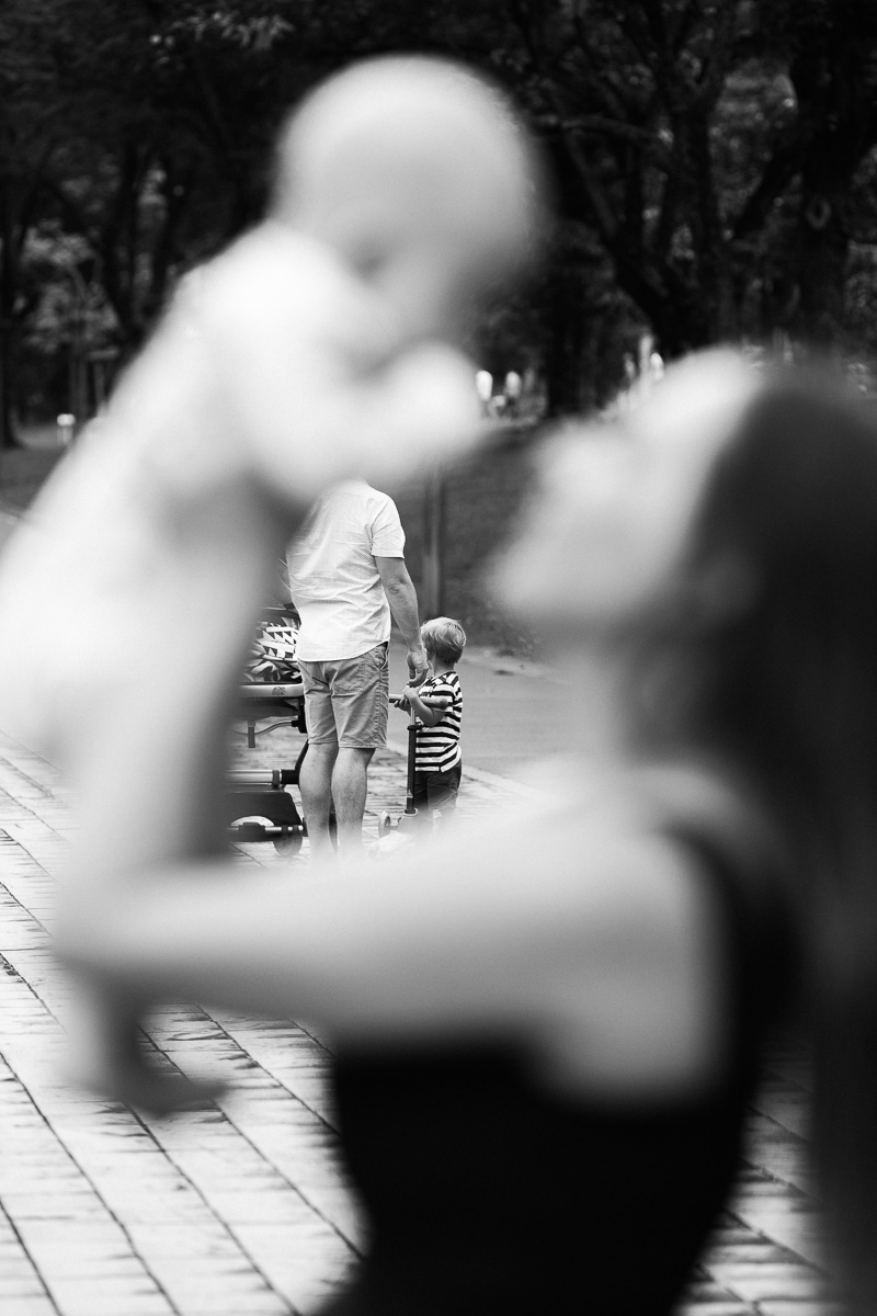 Kuala Lumpur Family Photographer Erica Knecht captures a dad holding his son's hand while in the foreground a mum kisses her baby.