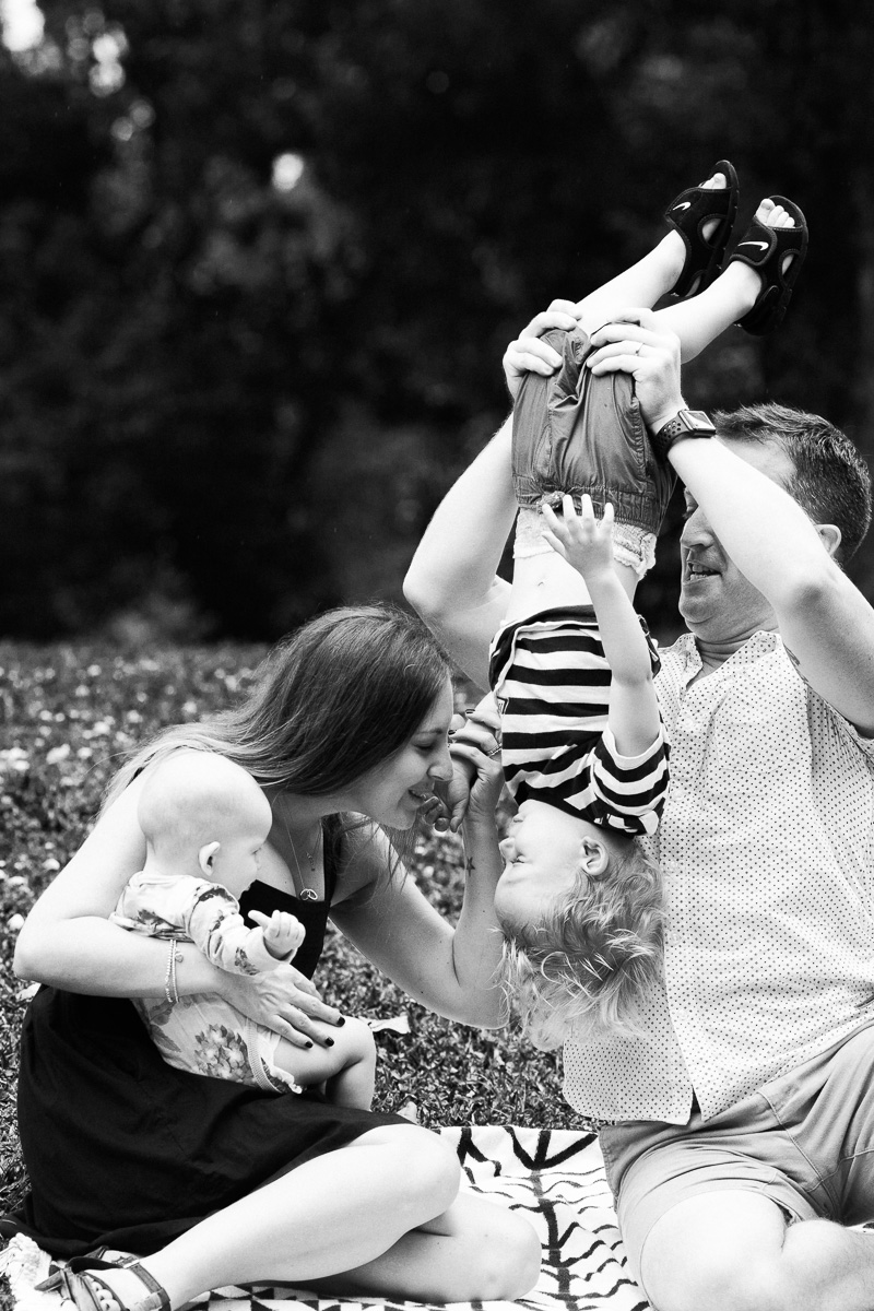 A family photography session in KLCC park featuring a dad holding his son upside-down while his mum looks on by top Asia Family Photographer, Erica Knecht.