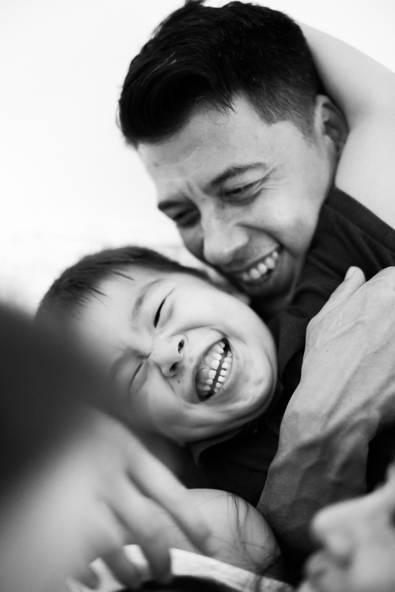 A father and young sun wrestle together as captured by Kuala Lumpur family photographer Erica Knecht
