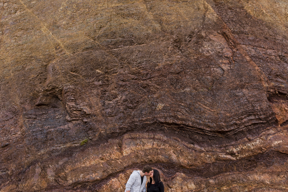 couple kissing in front of rocks