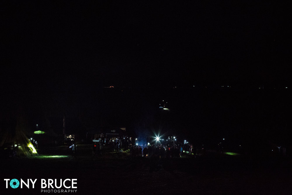 In the foreground competitors gather round the camp fire for a motivational speech from Coach Pain. At the top of the image late comers'  head torches can be seen as they wind their way down the valley.