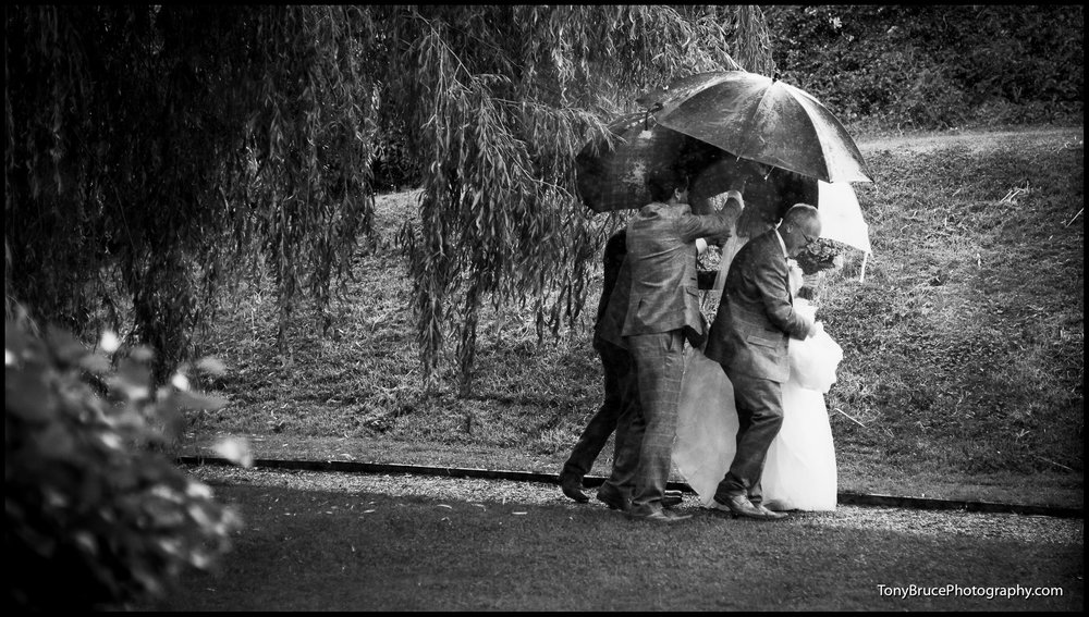 The Bride is protected from the driving rain.