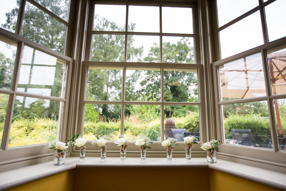Button holes sit on the window ledge of the bride's cottage.