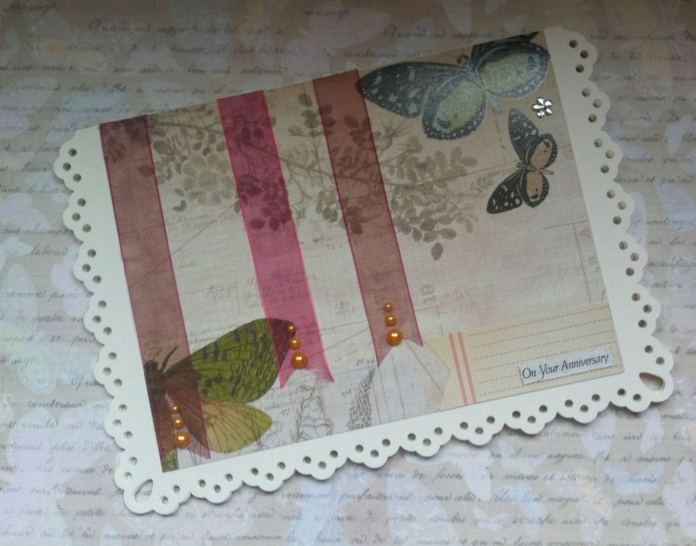 A homemade anniversary card with ribbon, pearls and scrapbook paper