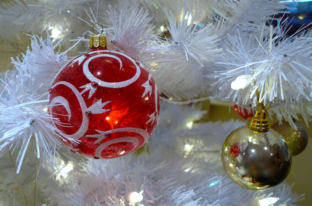 A HINT OF SPARKLE COMPLIMENTS THE WHITE GLITTER DECOR ON THE RED BAUBLE