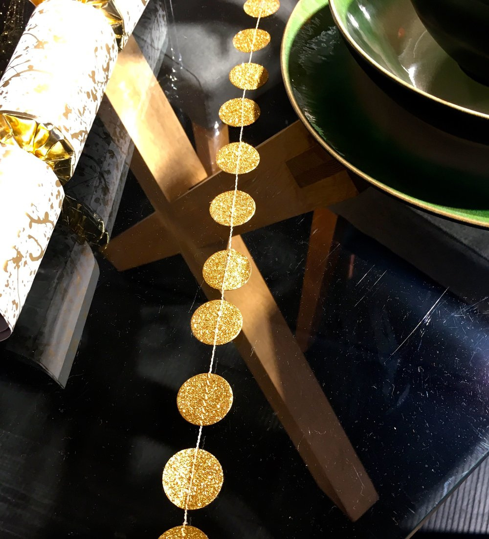 simple gold circle garland on a glass and wooden table