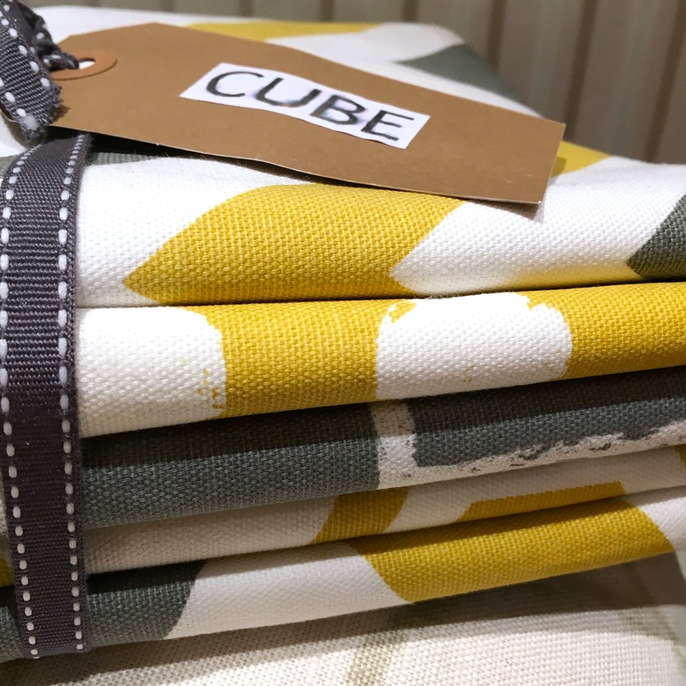 A stack of yellow white and grey geometric designed fabric