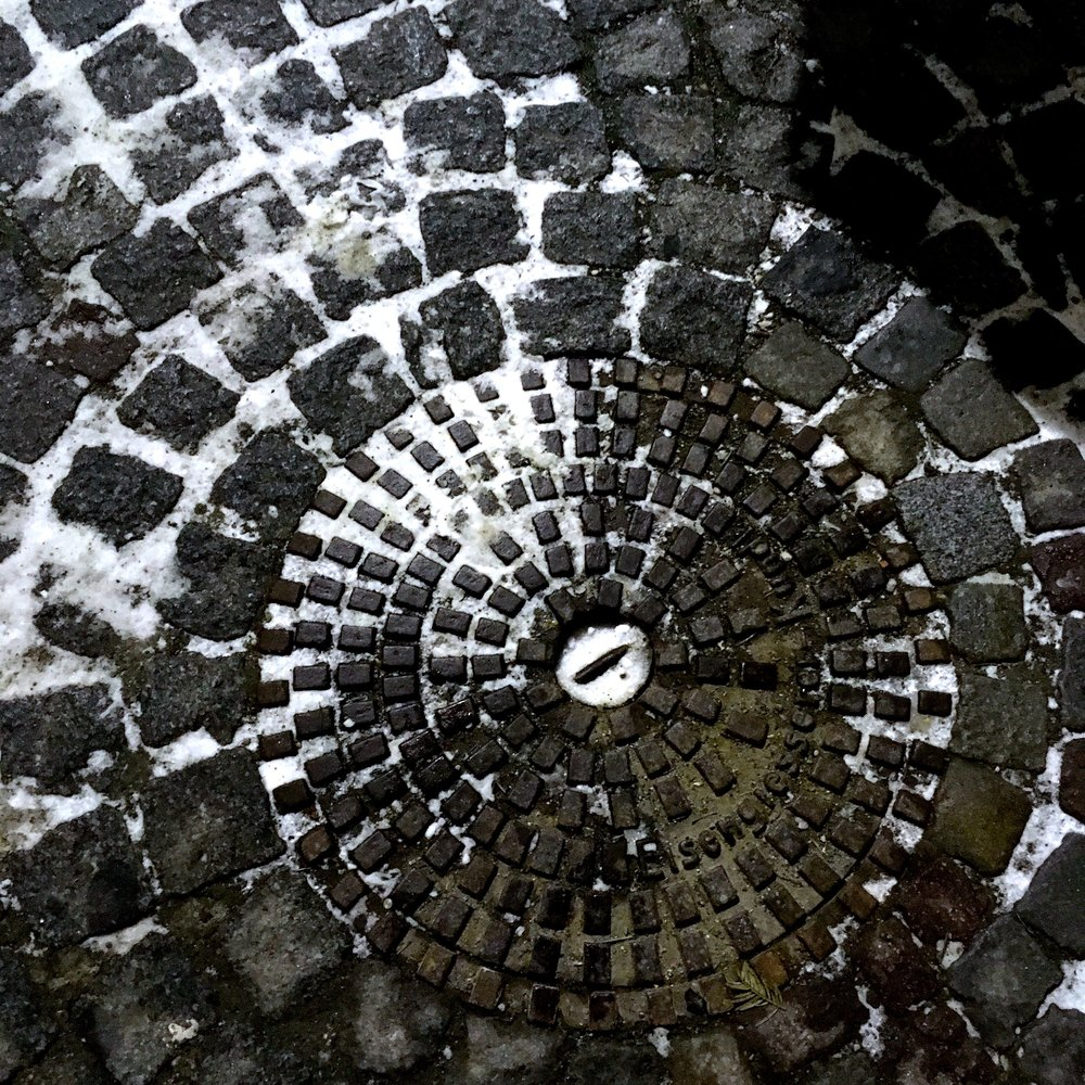 A SIMPLE DRAIN COVER, COBBLES AND A DUSTING OF SNOW