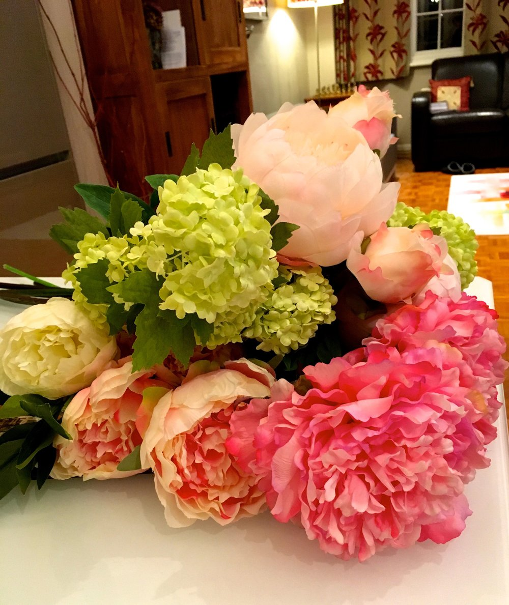 faux flowers piled onto the table with a realistic feel