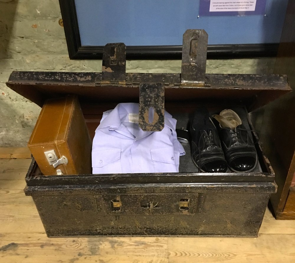 A serviceman's trunk with a serviceman's uniform and kit