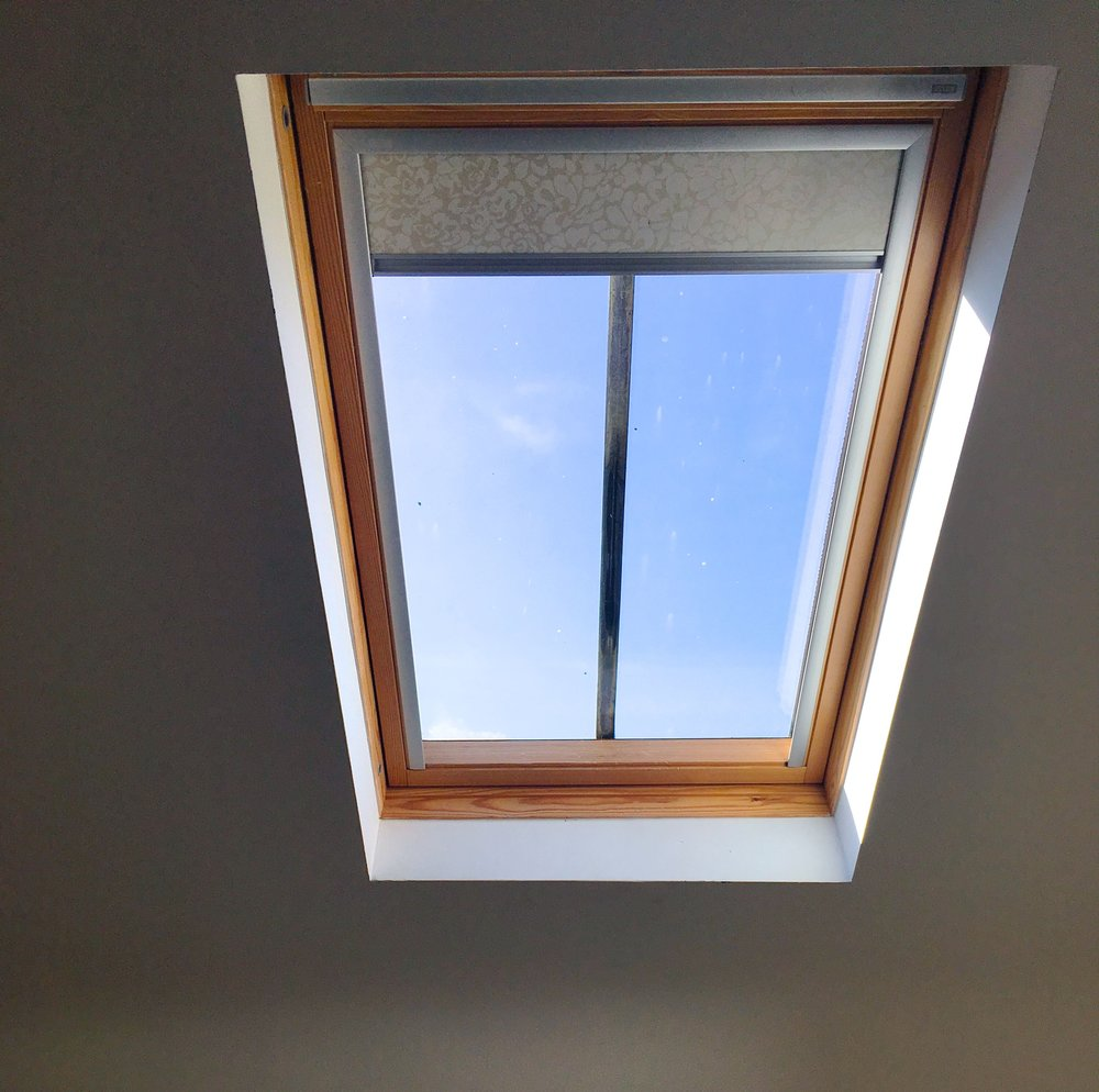 A velux window giving a glimpse of the blue skies