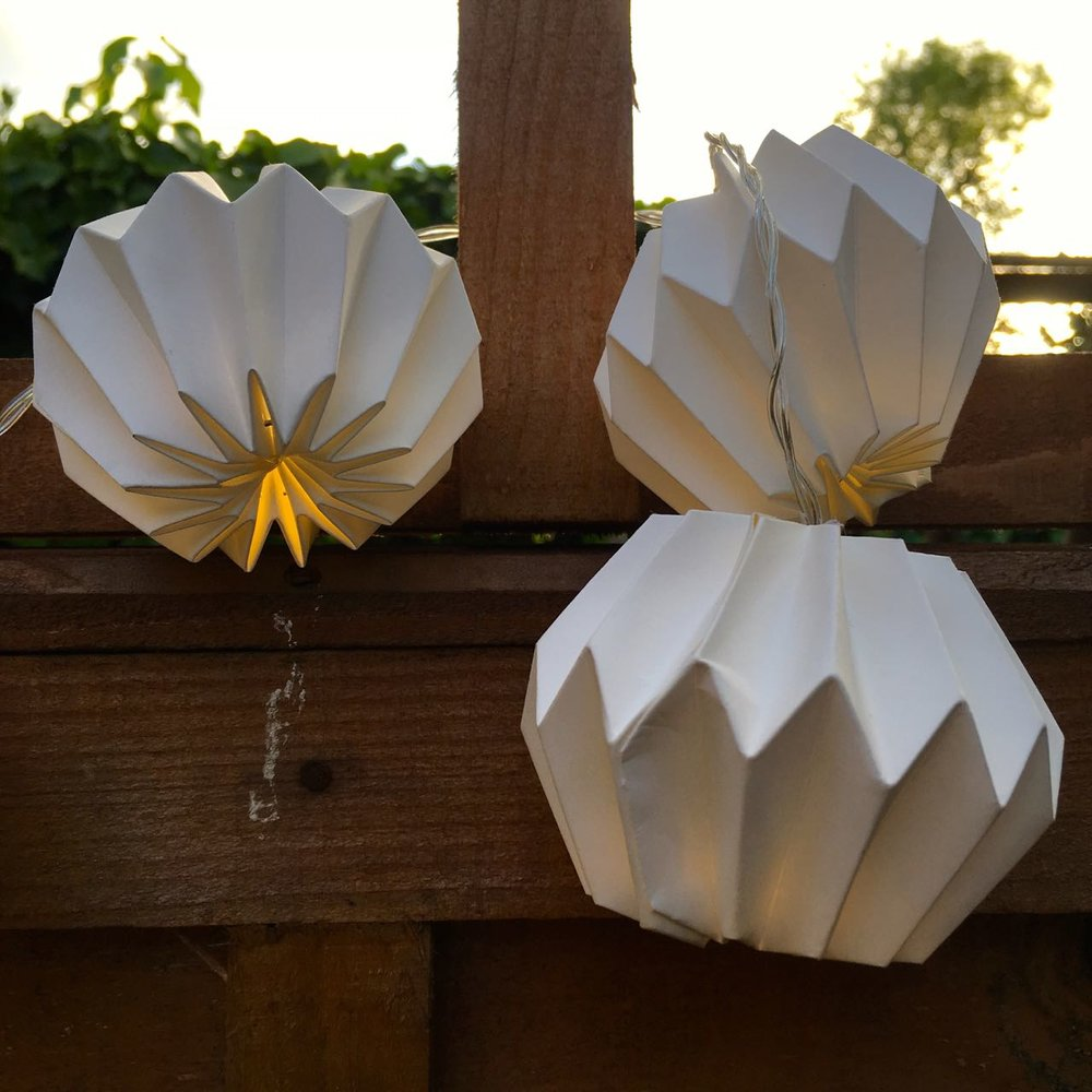 A string of paper lights by HomeSense adorning the fence