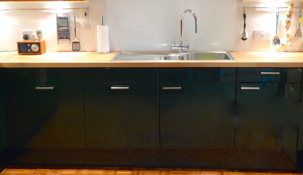 The dark green gloss base units, wooden worktop and chrome sink