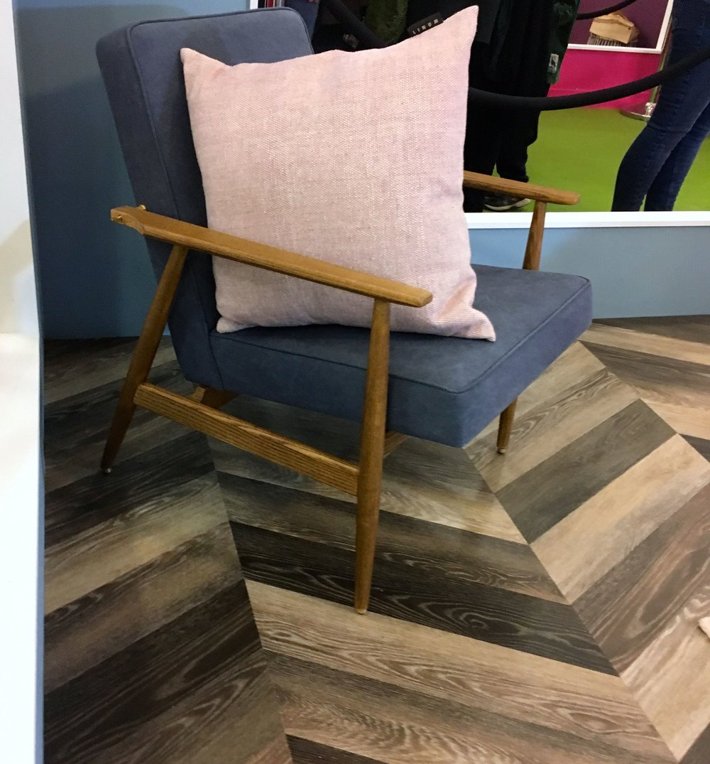 An armchair against the chevron floor  in the living room at the Ideal Home Show roomset