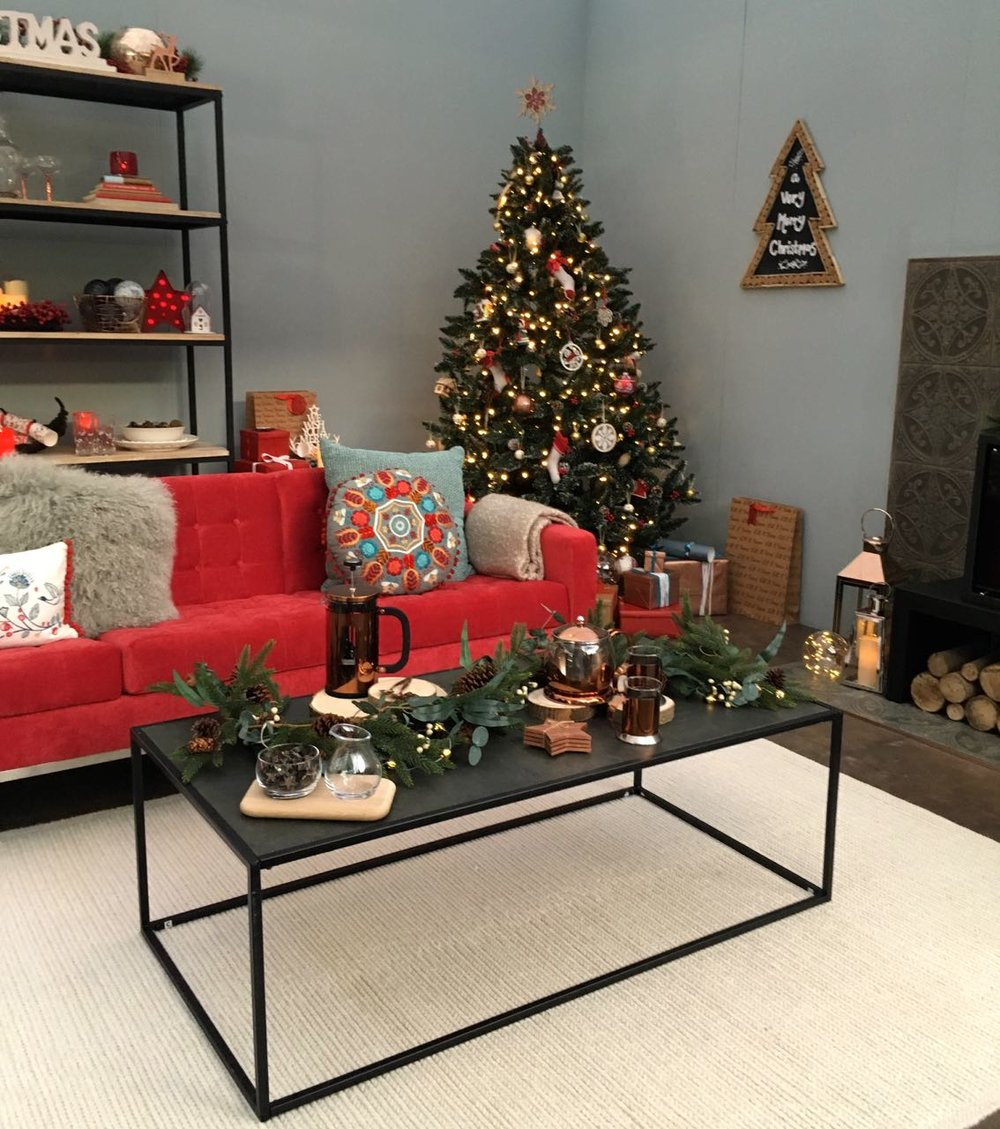 A coffee table and a christmas tree in the corner  in this room set at the Ideal Home Show at Christmas