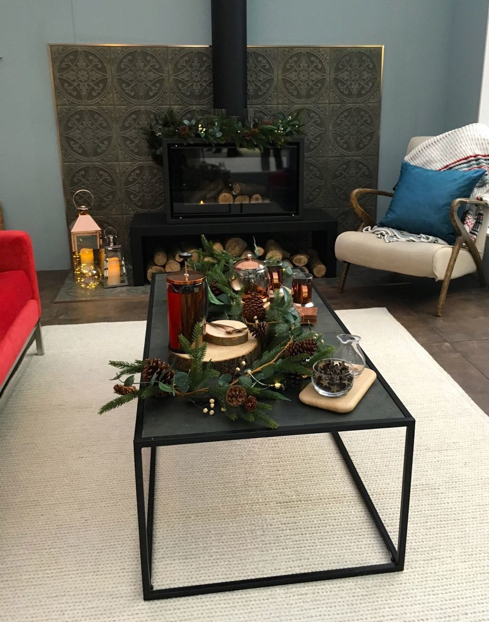 The wood burner and black metal coffee table  in this room set at the Ideal Home Show at Christmas