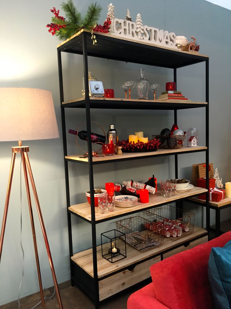 A matching open shelf unit and standard lamp  in this room set at the Ideal Home Show at Christmas