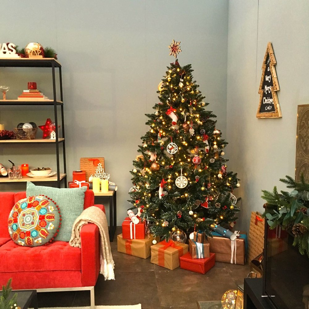 A tree and a berry red sofa in this folklore themed room set at the Ideal Home Show at Christmas