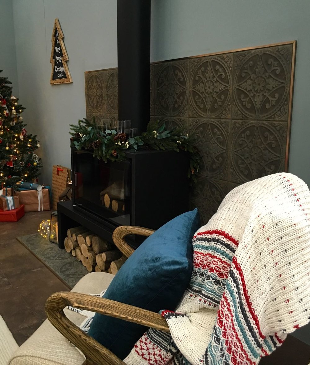 A cosy armchair in front of the wood burner  in this room set at the Ideal Home Show at Christmas
