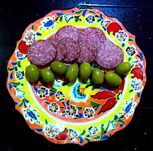 A COLOURFUL PLATE OF GRAND DESIGNS SALAMI AND OLIVES