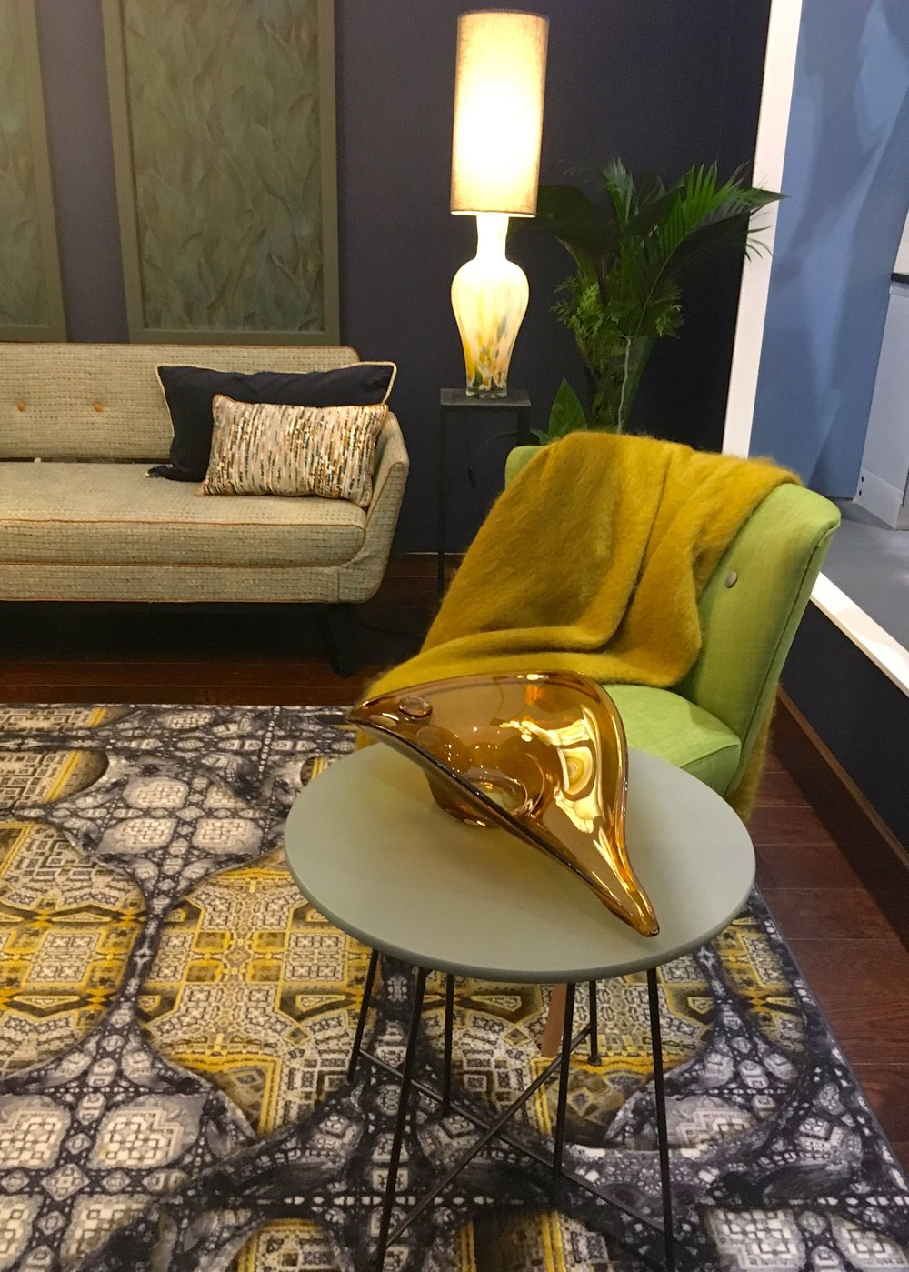 a lime green occasional chair, a patterned rug and comfy throw