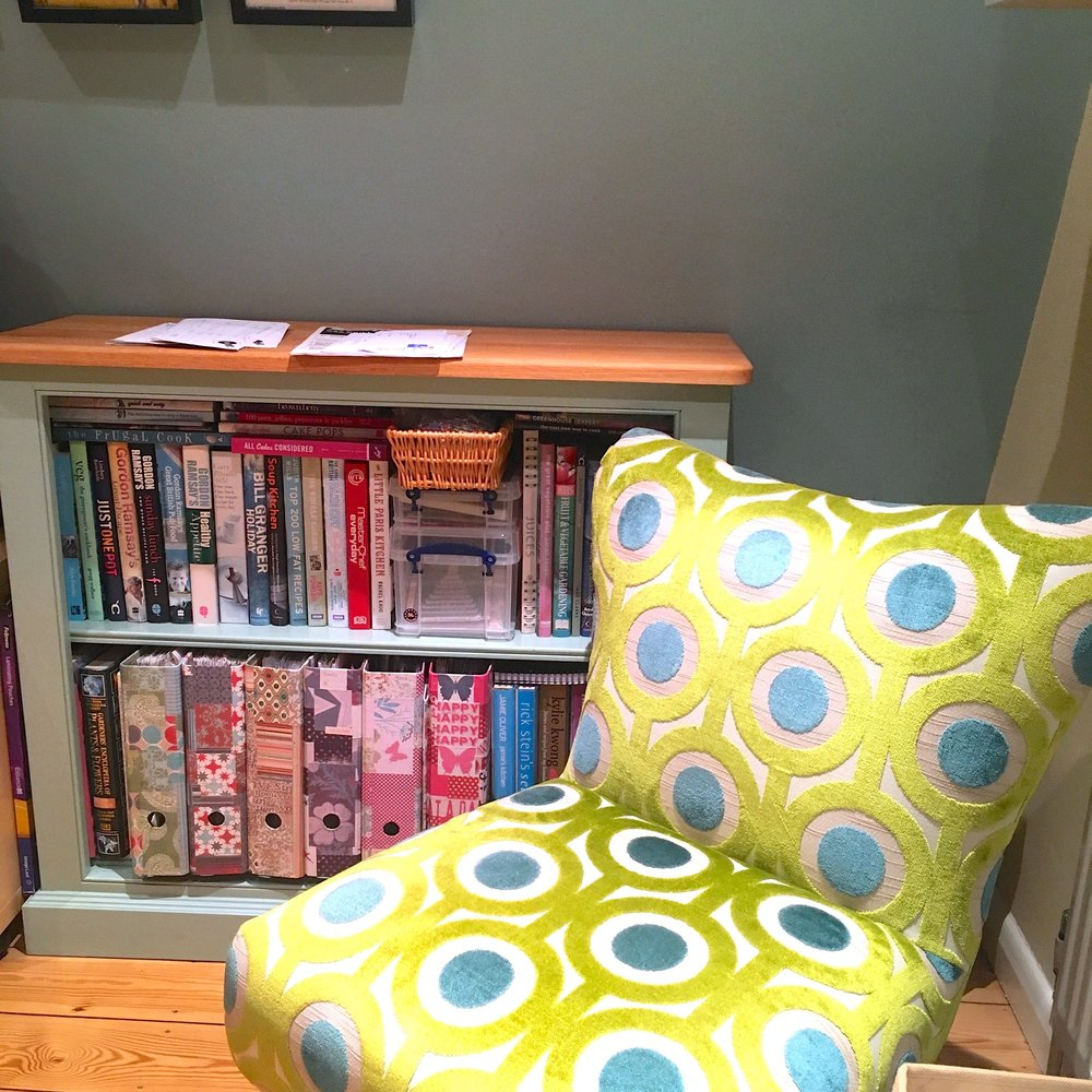 Books in the bookcase and a chair close by