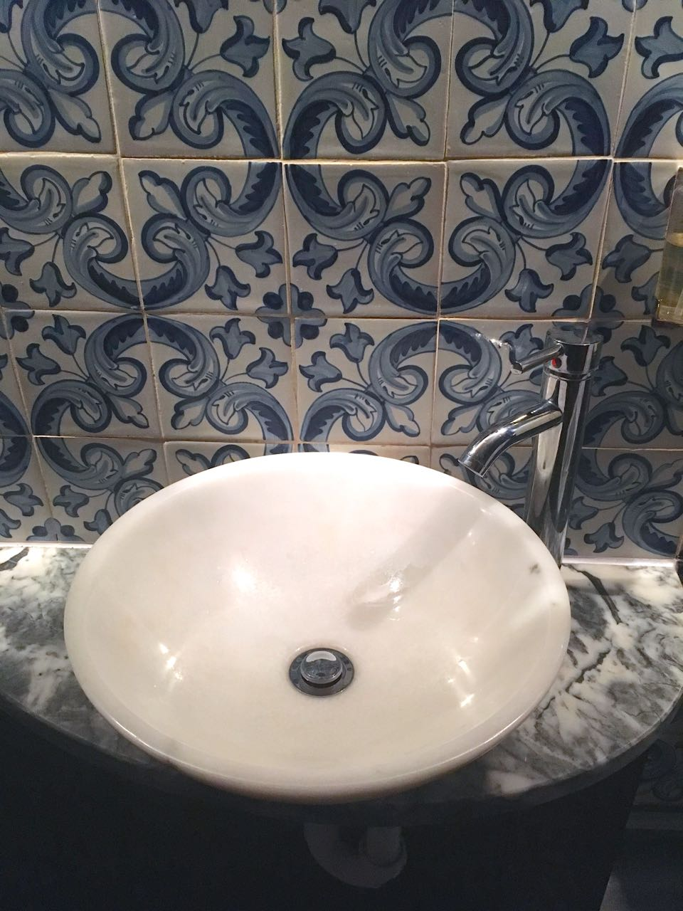 Blue and white tiles by the sink in the loos