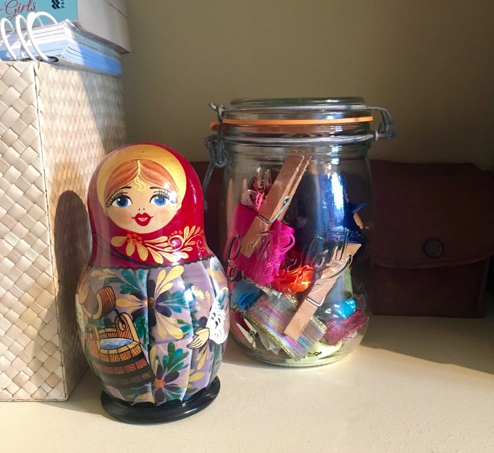 Russian doll and a jar of ribbons
