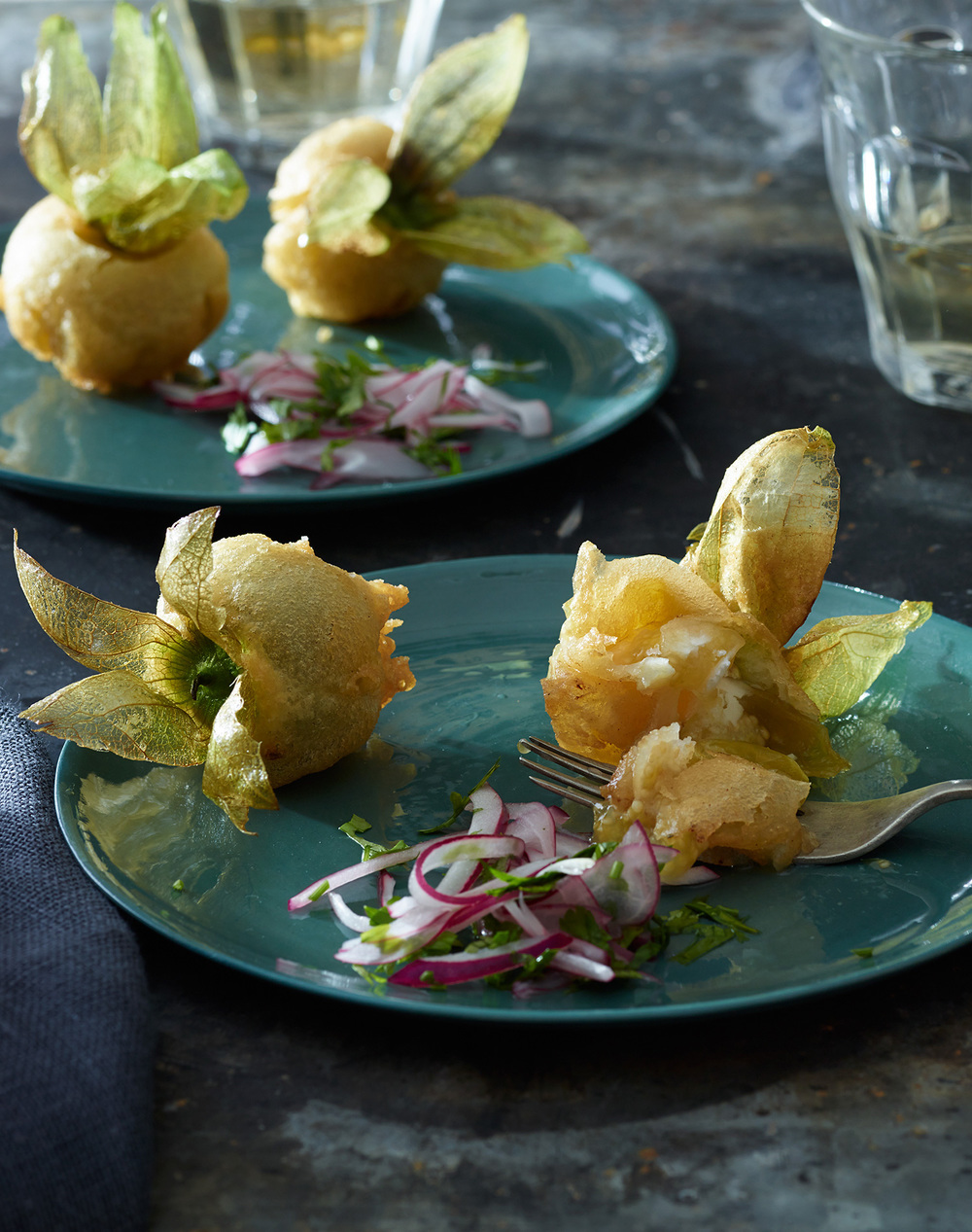 fried tomatillos with onion herb salad vinegar on a plate