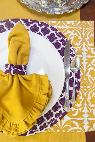Gold napkin on purple quilted placemat