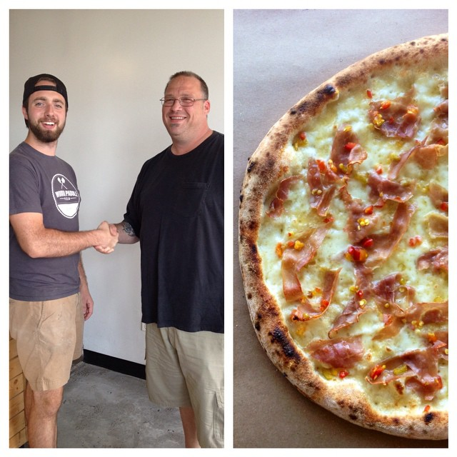 Owner Jon and pizza friend Jeff Valentino shaking hands over a pizza well done.