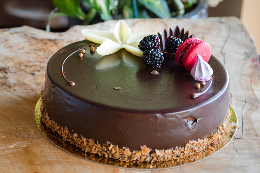Chocolate Raspberry Delice - The chocolate raspberry delice is a classic chocolate sponge cake with milk chocolate mousse, fresh raspberries, and chocolate ganache on the outer layer. Six-slice cake 30 / twelve-slice cake 48