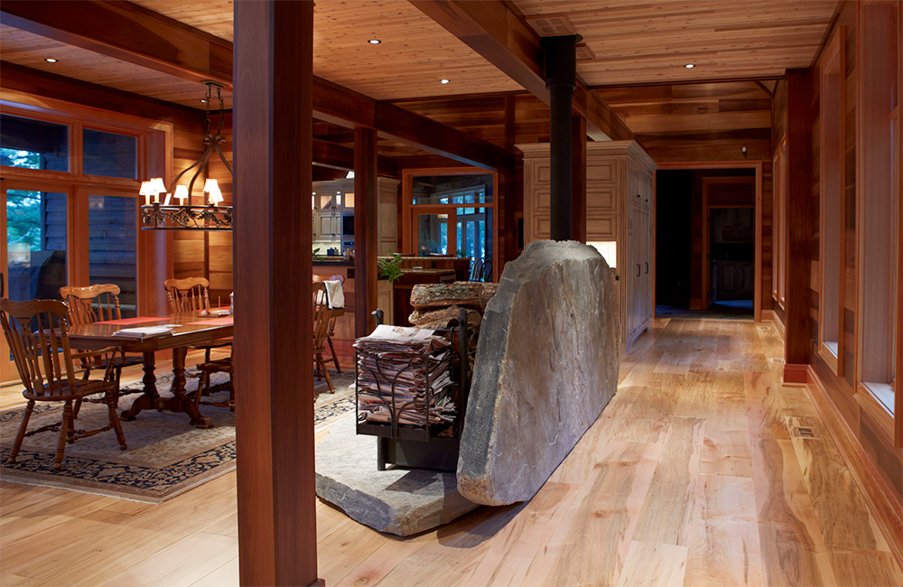 "The dining room, adjacent to the kitchen, simply furnished, is ""decorated ""by the radiant Lindal post and beam structure and is separated from the main hallway by only this massive slab of indigenous stone…."