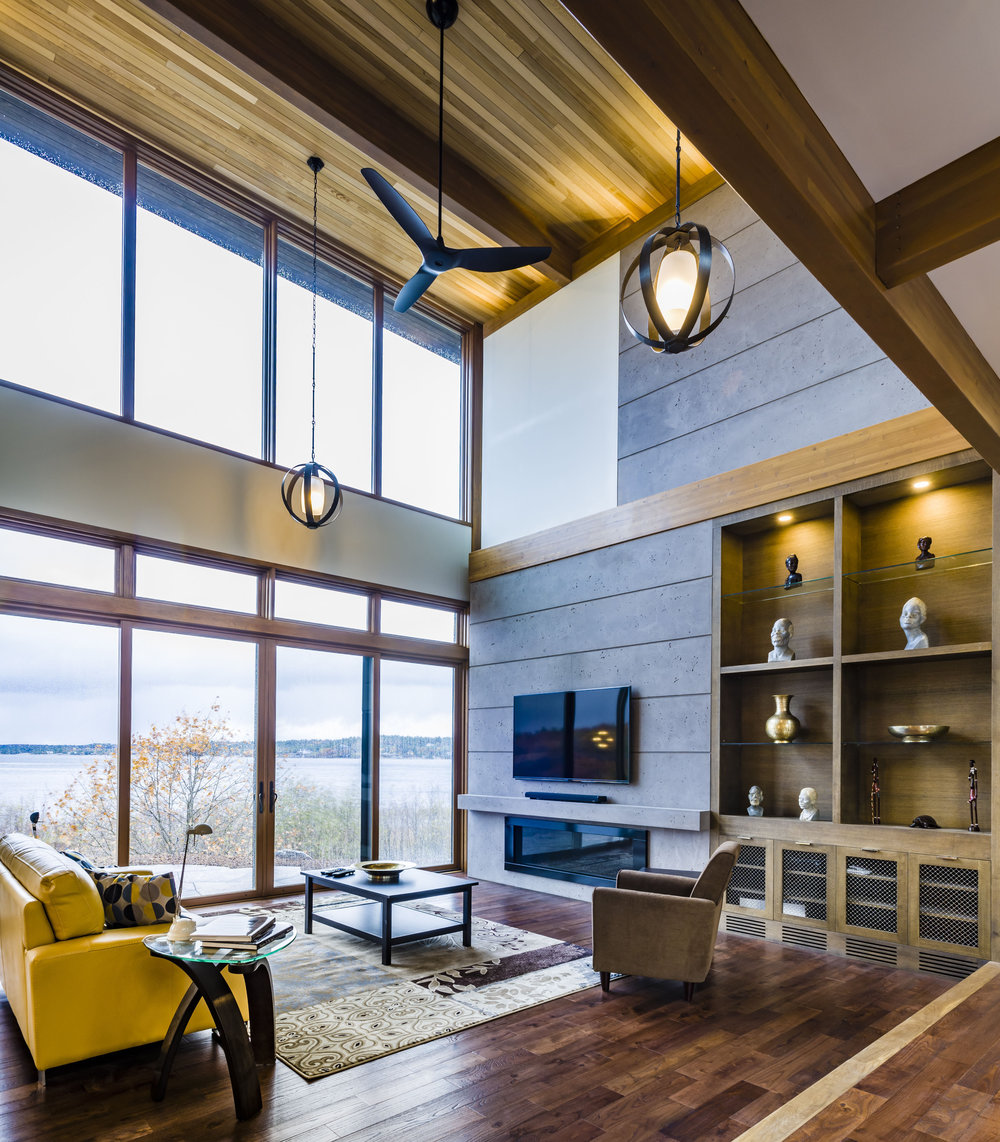 The sheetrock header over doors, trim band above the fireplace, and built-ins maintain the human scale in a 17-foot-high space.