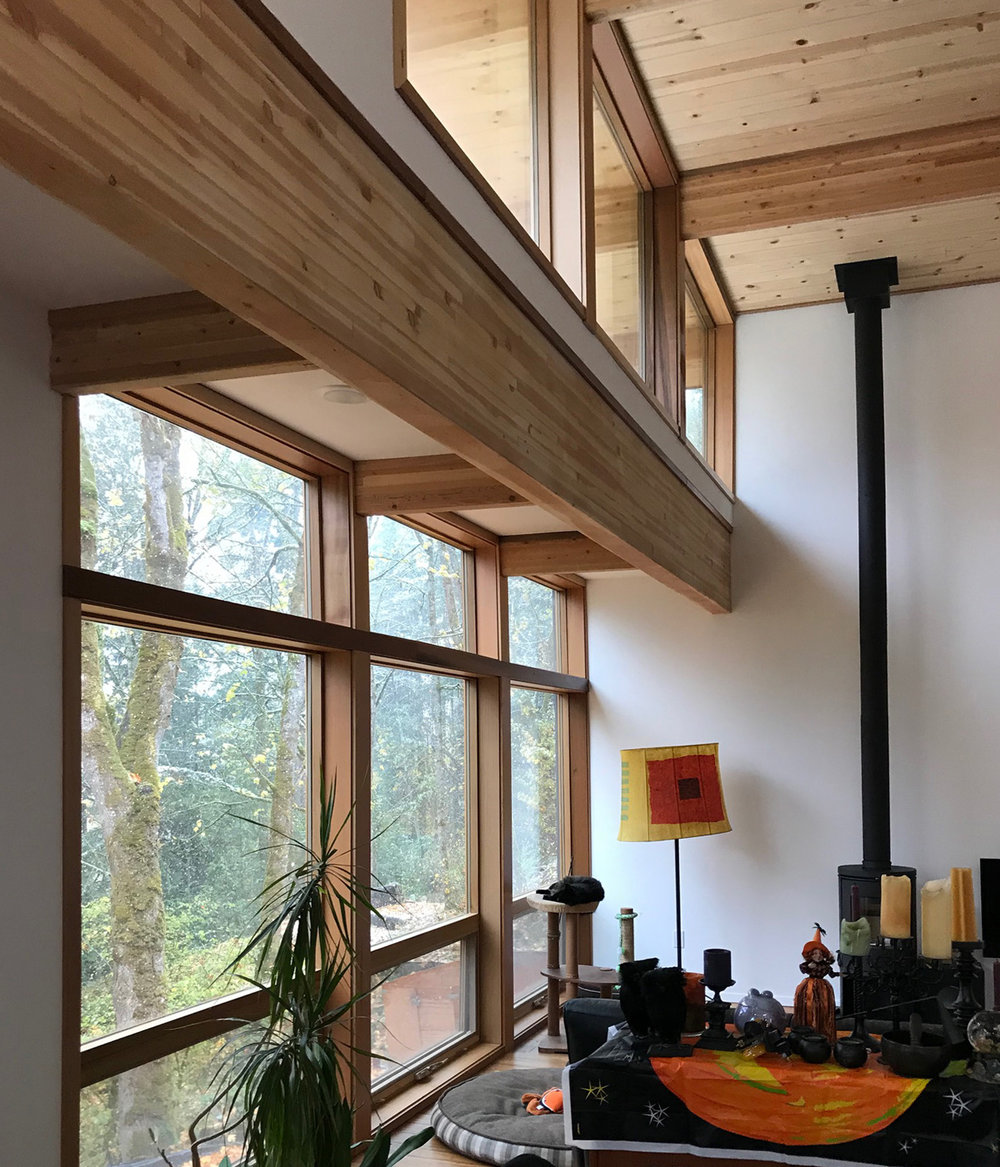 A flat roof over the last two feet of this area brings a high space into scale, provides alighting soffit, and brings natural daylight further into the room through the upper wall.