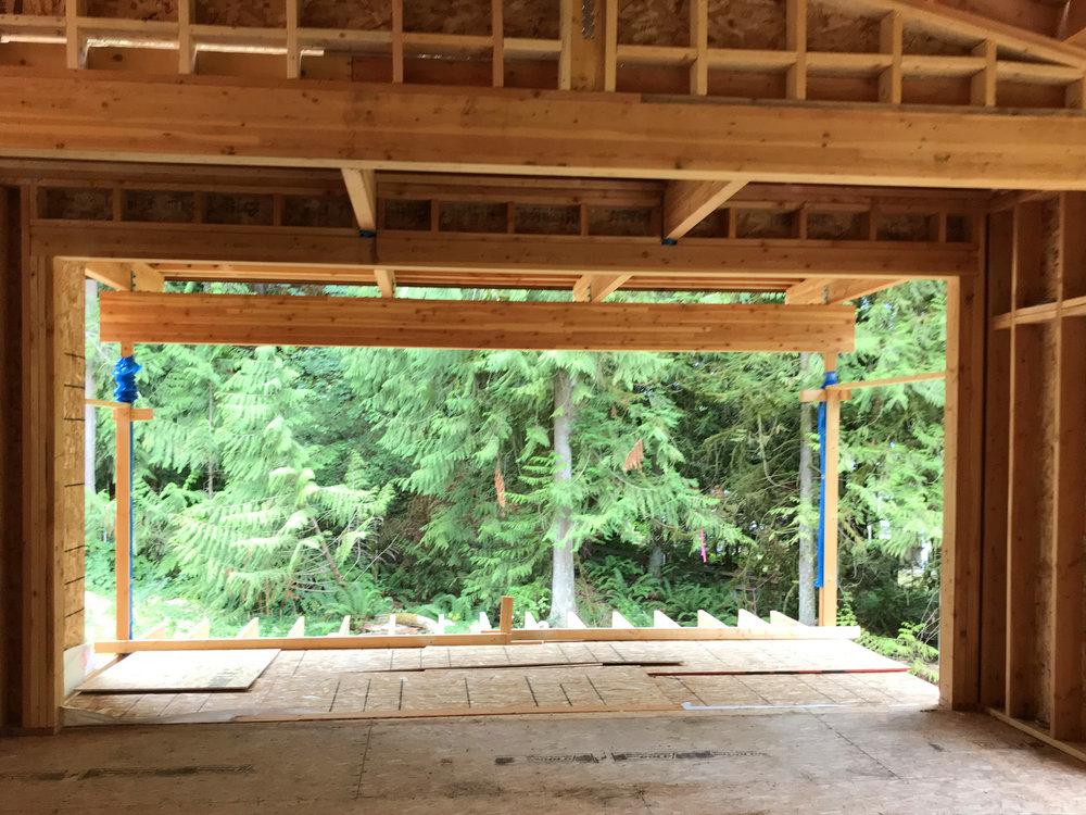 "The beautiful and strong Lindal laminated Douglas fir beams make ""easy lifting"" of wide openings, here a series of 16' openings… into the dining room, out onto the covered deck beyond, and at the outside corners of the deck. No additional support required!"