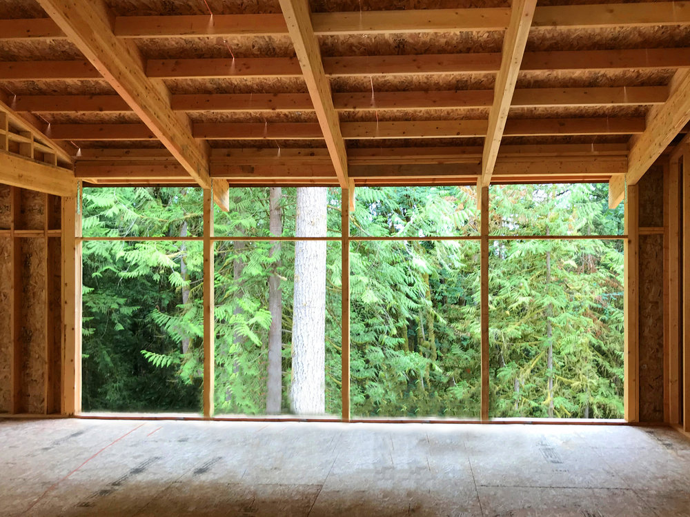 "The roof beams are supported at the front, center, and rear of the house by laminated posts. The standard 5'4"" spacing between the posts is all the support required. A 9' 5"" high by 22' wide expansive glass view wall will be interrupted by only three 3 1/2"" posts! Note how the laminated beams draw your eye through the window wall to the view beyond."