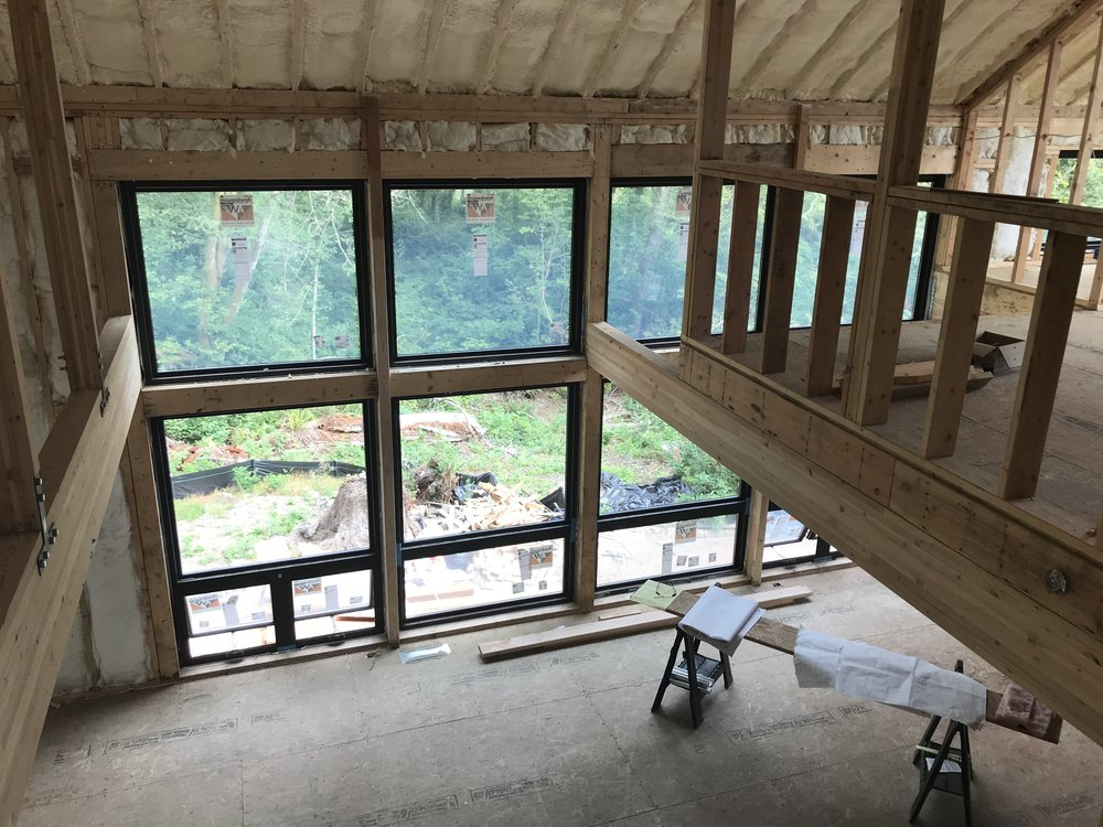 The view from the upper level office through the great room and to the view beyond