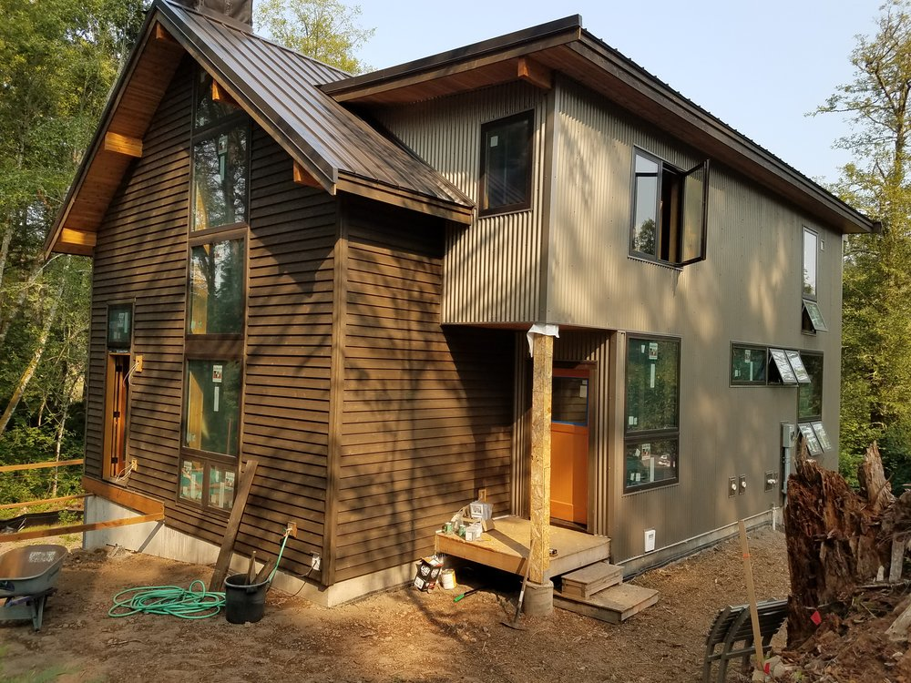 The entry dormer, clad in corrugated steel,  contrasted against the cedar siding, overhangs, and lam beams of the main house form