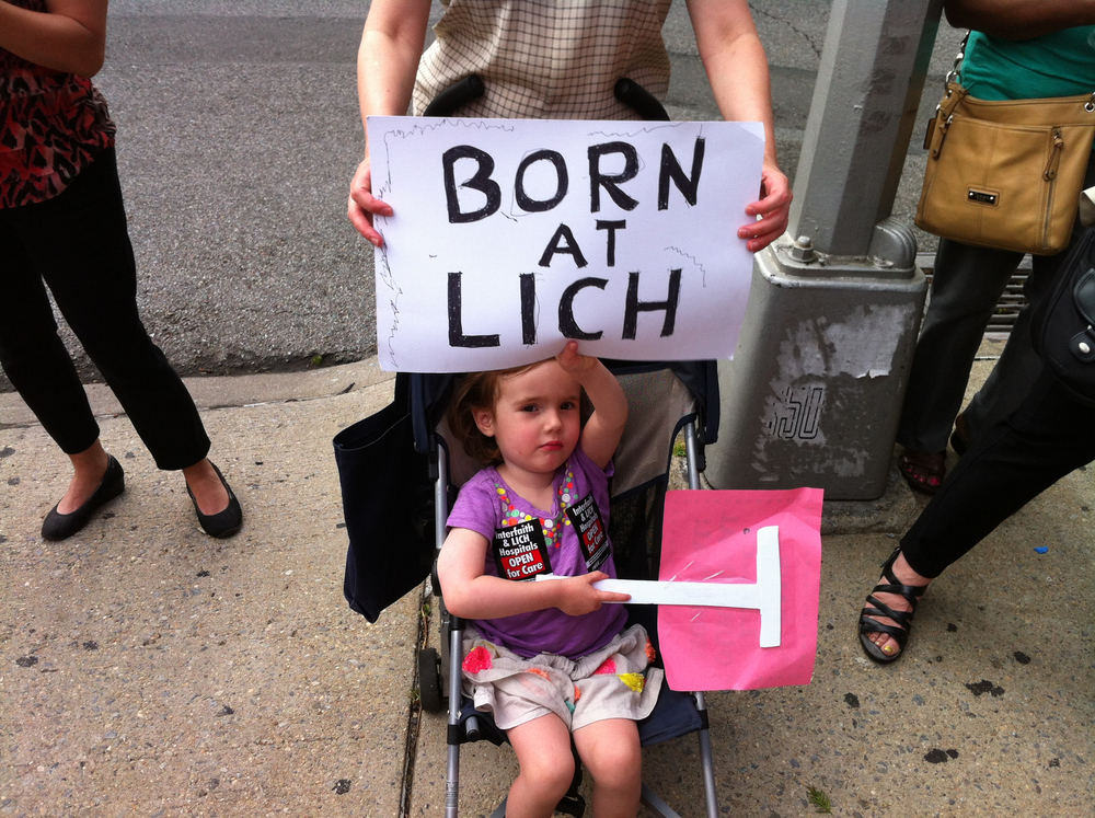 A toddler holds up a protest sign at a rally outside Long Island College Hospital on June 23, 2013.  Source :  Louis Flores