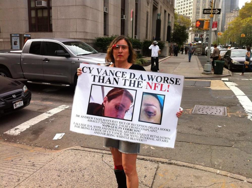 Suzannah B. Troy holds up a protest sign, showing the black eye she received as a result of an assault and battery, which the Manhattan District Attorney's Office refuses to prosecute.  SOURCE :  Louis Flores