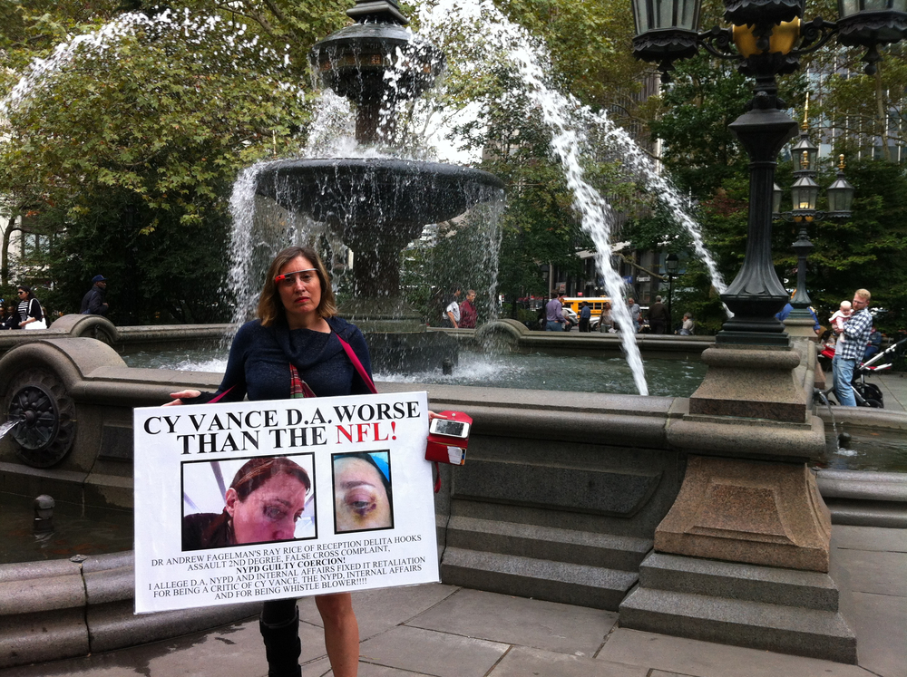 The artist and political blogger Suzannah B. Troy stood near the fountain at City Hall Park with her protest sign.  Activists distributed cards and flyers with information about the upcoming NYPD Five Points March for Reform. Source :  Louis Flores