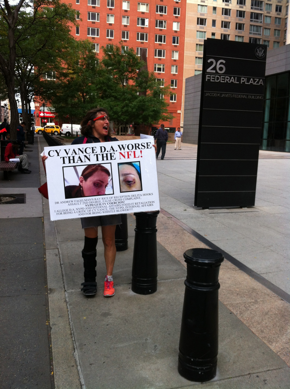 Ms. Troy, holding her protest sign outside the New York City Field Office of the Federal Bureau of Investigation in Downtown Manhattan.  Source :  Louis Flores