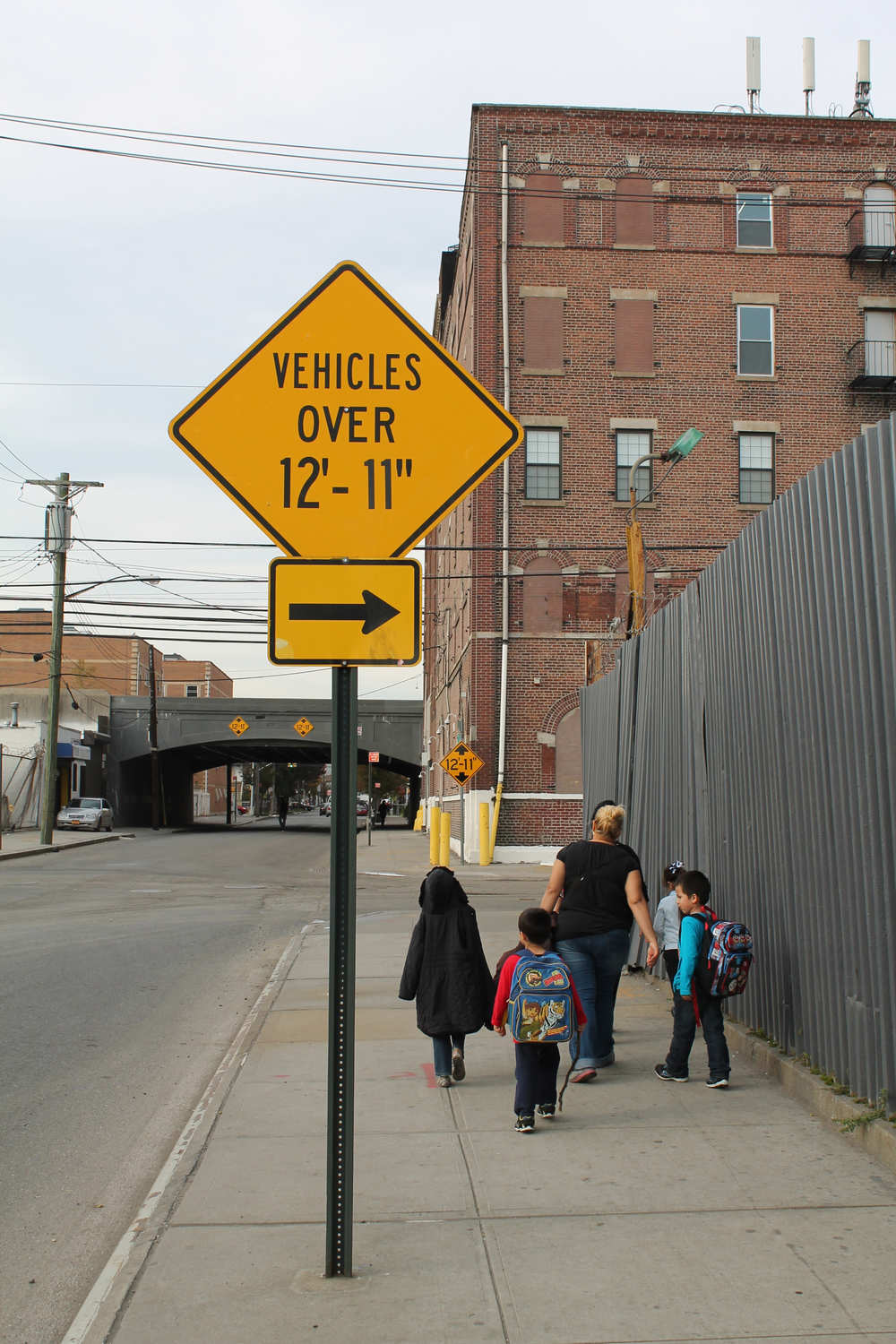 "The only visible traffic restriction along 170th Street is a ban on commercial trucks taller than 12'11"", which must turn east onto Douglas Avenue.  Trucks taller than that cannot clear the LIRR overpass in the background.  Some community residents believe that this traffic sign may implicitly approve the use of 170th Street by shorter, but still large and heavy, commercial trucks.   Source :  Louis Flores"